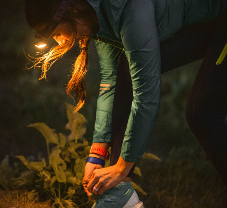 Woman using warm light headlamp to tie her shoes