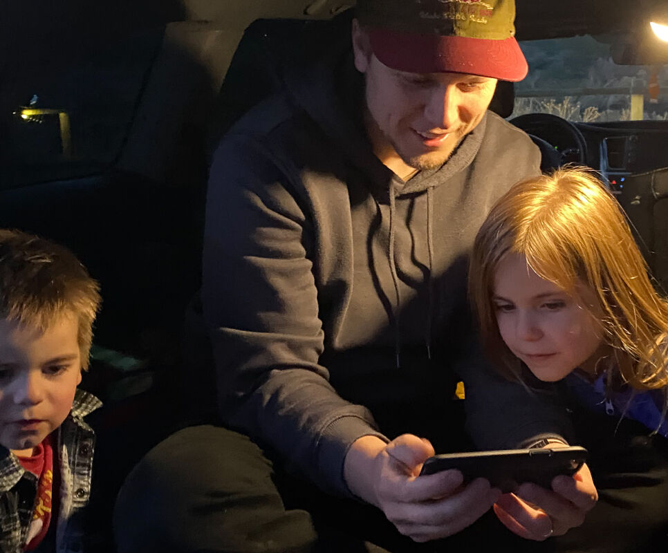 Dad watching a video on his phone with two kids using a portable lantern